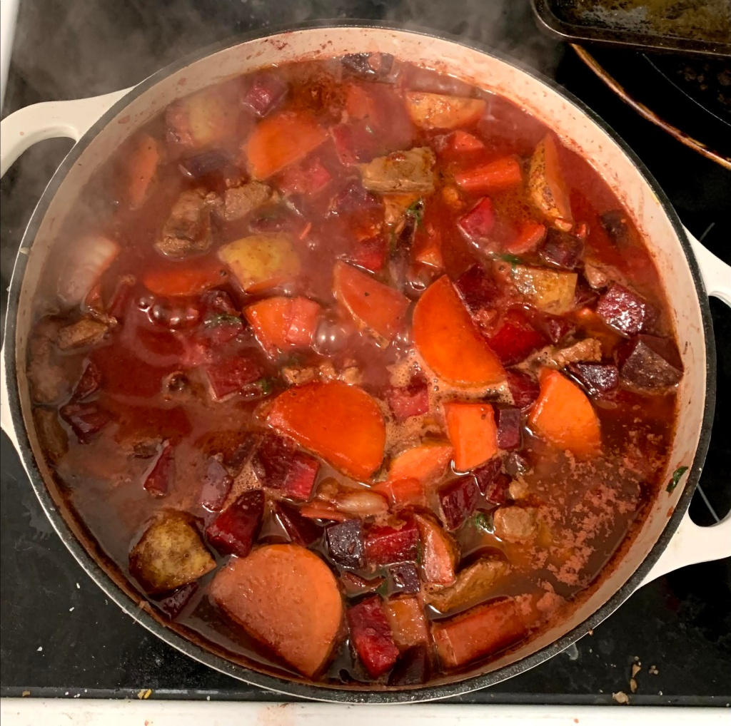 a steaming white pot on a black stovetop, filled to the brim with beets, potatoes, onions, beef liver, and broth being cooked into borscht.