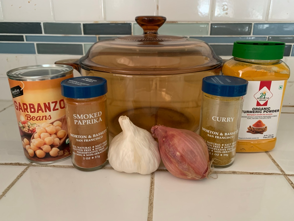 An empty glass pot sits on a counter, surrounded by a can of chickpeas, spices in bottles, a head of garlic, and a shallot.