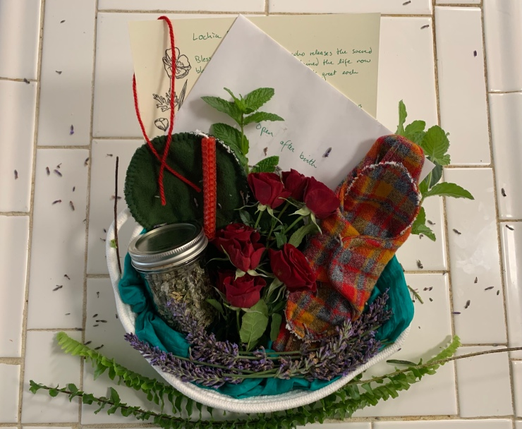 A cloth basket lined with blue cloth sits on a white counter, framed at the bottom with ferns. Clockwise from top left, the basket holds a handwritten paper titled 'lochia,' a red string hanging on the left corner of the paper, an envelope partially covering the paper titled 'open after birth,' mint sprigs, a red, blue, and yellow plaid cloth menstrual and lochia pad snapped around its liner, lavender framing the inside bottom of basket, small red roses, a small mason jar with herbal tea blend, a red candle, and two dark green cloth nursing pads. Lavender petals are scattered on the white tile background.