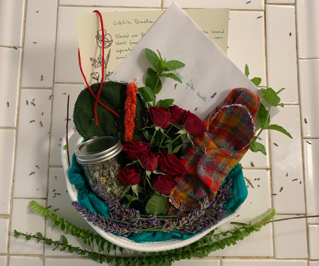 A cloth basket lined with blue cloth sits on a white counter, framed at the bottom with ferns. Clockwise from top left, the basket holds a handwritten paper titled 'lochia bracha,' a red string hanging on the left corner of the paper, an envelope partially covering the paper titled 'open after birth,' mint sprigs, a red, blue, and yellow plaid cloth menstrual and lochia pad snapped around its liner, lavender framing the inside bottom of basket, small red roses, a small mason jar with herbal tea blend, a red havdalah candle, and two dark green cloth nursing pads. Lavender petals are scattered on the white tile background.