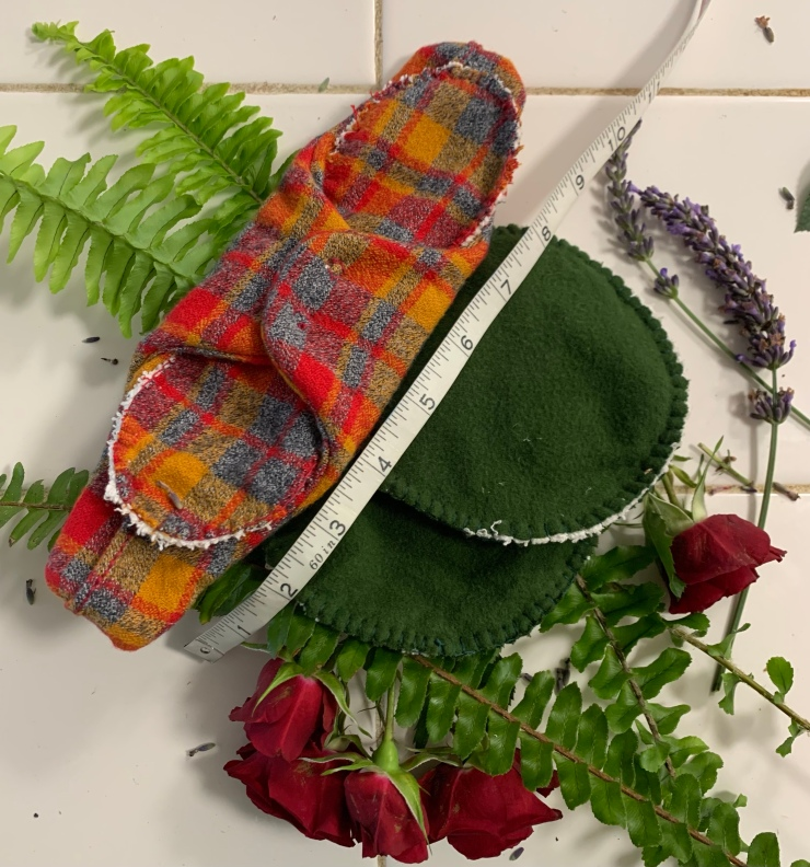 A red, blue, and yellow plaid cloth menstrual and lochia pad sits snapped around its liner with a pair of dark green nursing pads to the right, with a tape measure showing the lochia pad about 10 inches in length and the nursing pads 5 inches in diameter. They sit on a white counter resting on ferns, small red roses, and lavender.