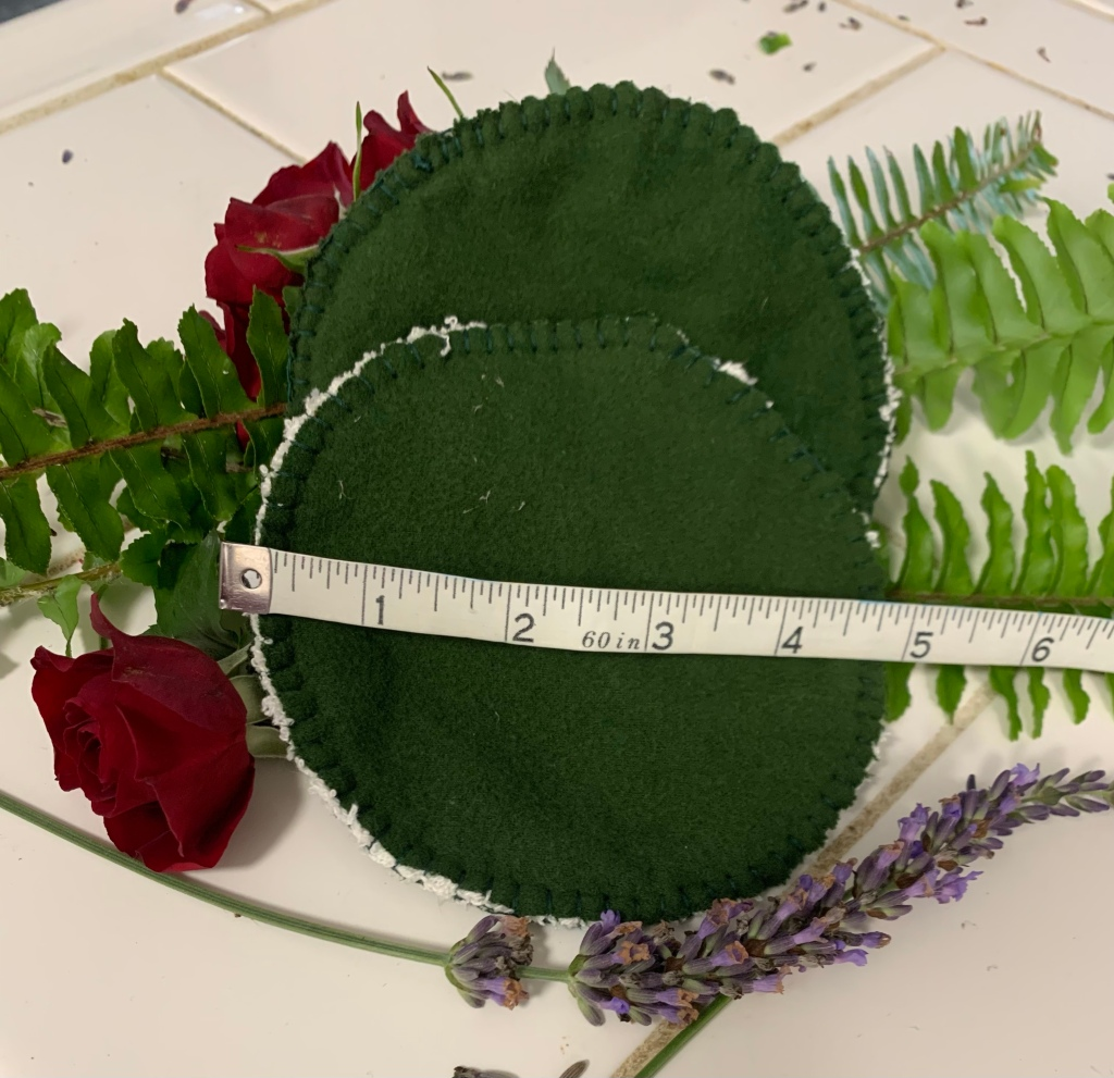 a pair of dark green cloth nursing pads rest on a white counter against ferns, small red roses, and lavendar with a measuring tape showing their diameter at 5 inches.
