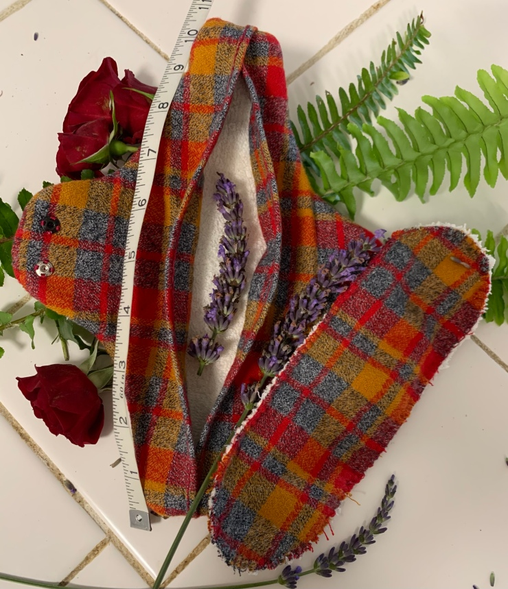 A red, blue, and yellow plaid cloth menstrual and lochia pad liner and insert sit on a white counter resting against ferns and small red roses. Lavender flowers separate the liner from pad and one sits inside the unsnapped and opened liner to show extra absorbent construction. A measuring tape shows it to be about 10 inches in length.